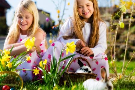 huevos de pascua: Niños en una caza del huevo de Pascua en un prado en primavera, la vida de Pascua está sentado en la cesta de Pascua