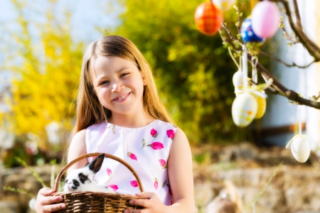 Little girl on Easter egg hunt in the spring, an Easter bunny is sitting in a basket photo