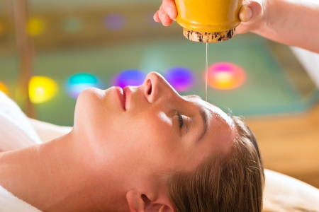 Woman enjoying a Ayurveda oil massage treatment in a spa  photo