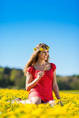 Young girl sitting in spring on a flower meadow with dandelion photo