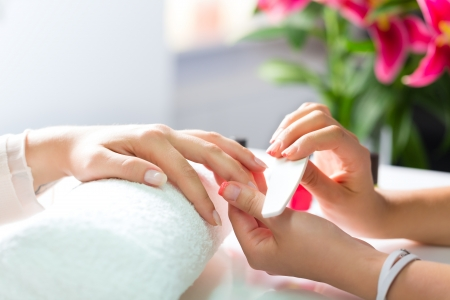 manicurist: Woman in a nail salon receiving a manicure by a beautician Stock Photo