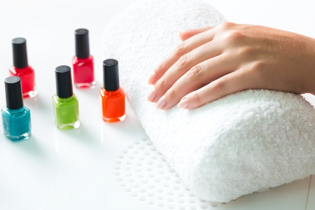 Woman in a nail salon receiving a manicure, there are colorful nail polish Stock Photo - 17324700
