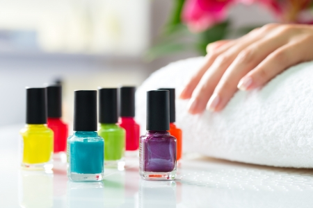 salon: Woman in a nail salon receiving a manicure, there are colorful nail polish