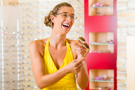 Young woman at optician with glasses, she might be customer or salesperson photo