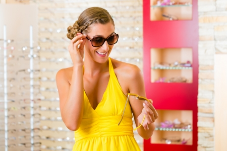 might: Young woman at optician with glasses, she might be customer or salesperson and is wearing sunglasses Stock Photo