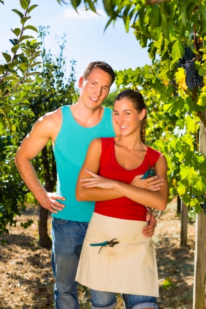 winegrowing: Winegrower, Woman and man standing at vineyard and smiling in the sunshine