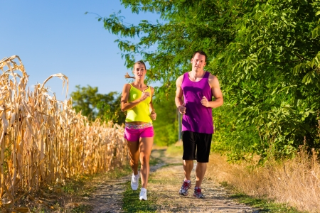 dirtroad: Rural sports - couple jogging for fitness on a beautiful summer day Stock Photo