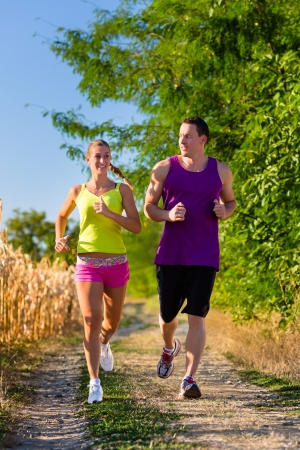 Rural sports - couple jogging for fitness on a beautiful summer day photo