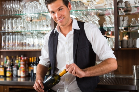 Barman standing behind the bar In restaurant opening a wine bottle photo
