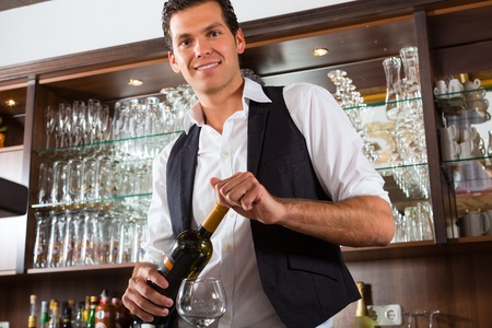 barman: Barman standing behind the bar In restaurant opening a wine bottle