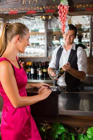 Smiling woman ordering a glass of wine at bar in Restaurant or Hotel Stock Photo - 17324909