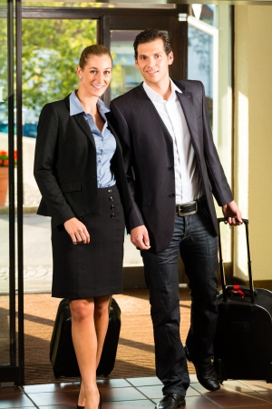 mujer con maleta: Los hombres de negocios que llegan al hotel con las maletas