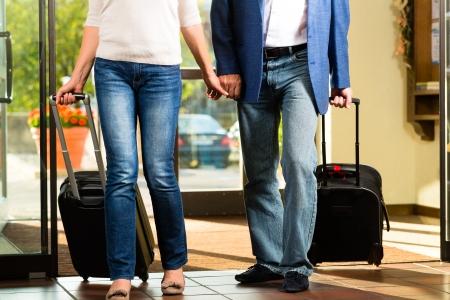 mujer con maleta: Hombre mayor y mujer - matrimonio - llegando al hotel con su equipaje