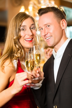 Couple, man and woman, drinking champagne in a fine dining restaurant, each with glass of sparkling wine in hand photo