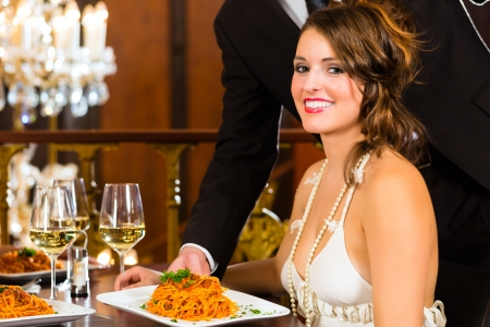 fine dining: Pretty woman sitting at a table in a fine dining restaurant, waiter served the dinner - a large chandelier is in Background Stock Photo