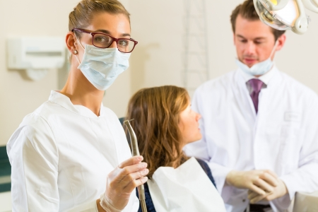 Dentists in his surgery holds a drill and looking at the viewer, in the background her colleague is giving a female patient a treatment Stock Photo - 17324720