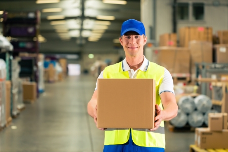 Warehouseman with protective vest and scanner, scans bar-code of package, he standing at warehouse of freight forwarding company Stock Photo - 17324846