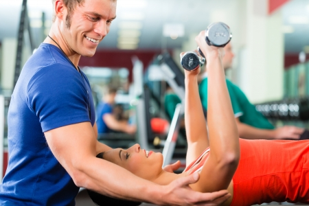 personal trainer: Woman with her personal fitness trainer in the gym exercising with dumbbells