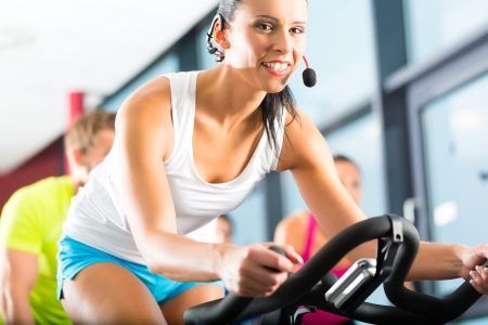 trainer: Young People - group of women and men - doing sport Spinning in the gym for fitness