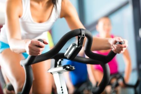 Jeunes - groupe de femmes et d'hommes - faire du sport Spinning dans la salle de gym pour le fitness Banque d'images