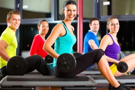 levantar pesas: grupo de gente joven deporte entrenamiento con pesas en un gimnasio para un mejor estado f�sico Foto de archivo