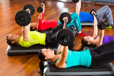 group of young sport people training with barbell at a gym for better fitness photo