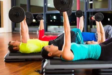 curso de capacitacion: grupo de gente joven deporte entrenamiento con pesas en un gimnasio para un mejor estado f�sico Foto de archivo