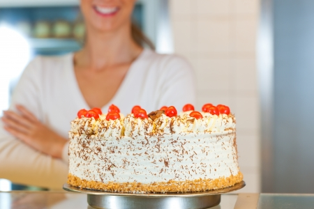 Female baker or pastry chef with torte in bakery photo