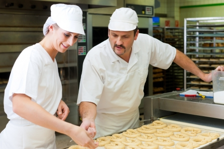 food production: Female and male baker baking fresh bread in the bakehouse, they produce brezn Stock Photo