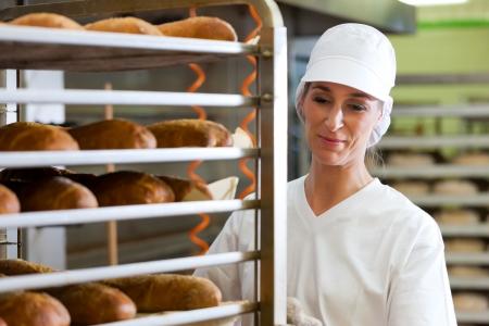 Female B�cker backen frisches Brot in der Backstube Lizenzfreie Bilder