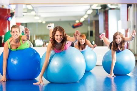 gimnasia ritmica: Fitness - Las mujeres j�venes haciendo el entrenamiento de deportes o hacer ejercicios con pelota de gimnasia en un gimnasio Foto de archivo