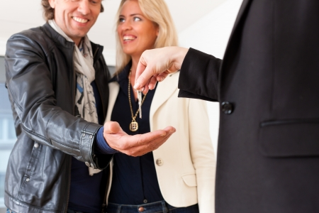 purchaser: Young realtor is giving the keys to an apartment to a young couple, maybe the purchaser or the tenants