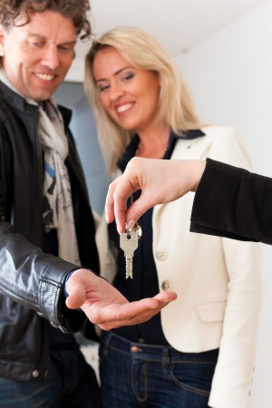 broker: Young realtor is giving the keys to an apartment to a young couple, maybe the purchaser or the tenants