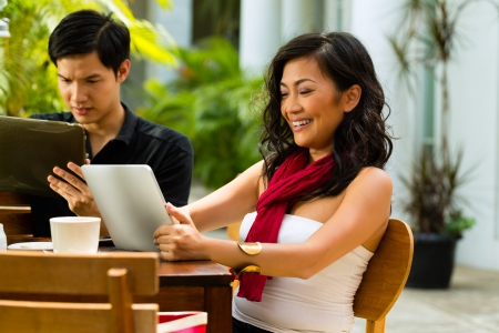 Asian woman and man are sitting in a bar or cafe outdoor and are surfing the internet with a tablet computer photo