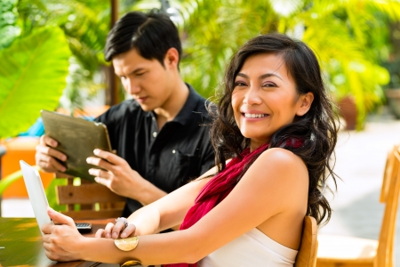 affluent: Asian woman and man are sitting in a bar or cafe outdoor and are surfing the internet with a tablet computer Stock Photo