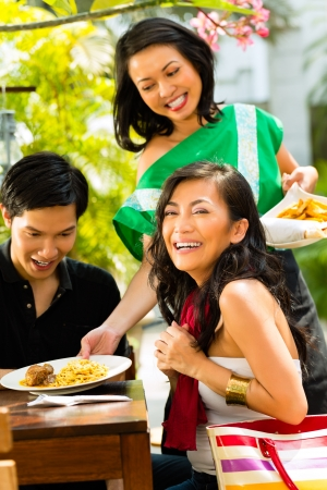 green dates: Asian man and woman in restaurant are being served food by the waitress Stock Photo