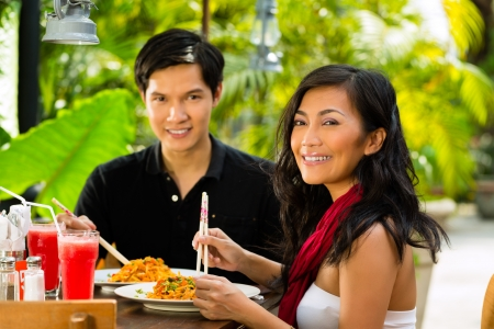 eating in: Asian man and woman in restaurant eating their food with chopsticks