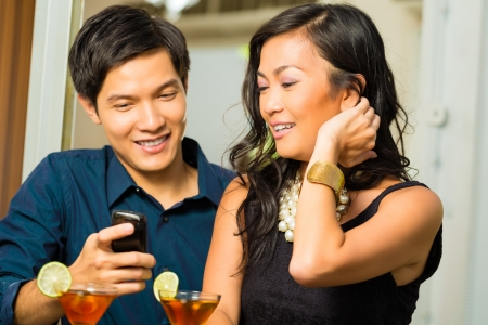 Asian man is flirting with woman in a bar while having drinks, woman is shy photo