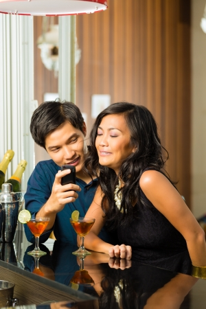 Asian man is flirting with woman in a bar having drinks, woman is shy photo