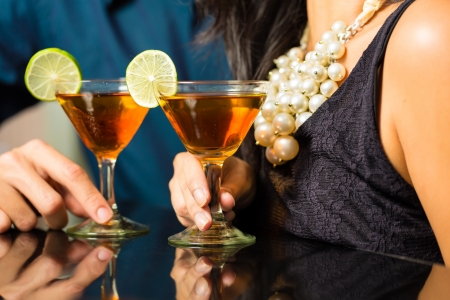 intimately: Man and woman flirting intimately at bar drinking cocktails  Stock Photo