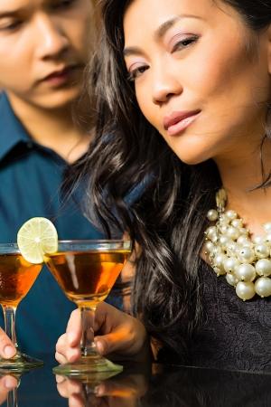 intimately: Asian man and woman in flirting intimately at bar drinking cocktails Stock Photo