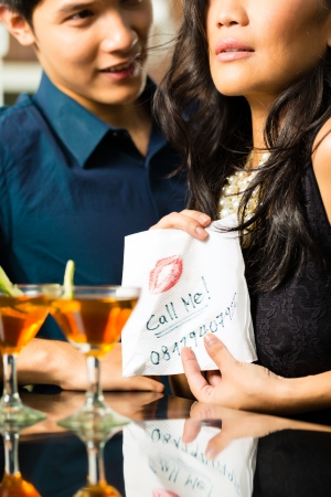Asian woman seduces the man in restaurant and gives him her number on a napkin photo