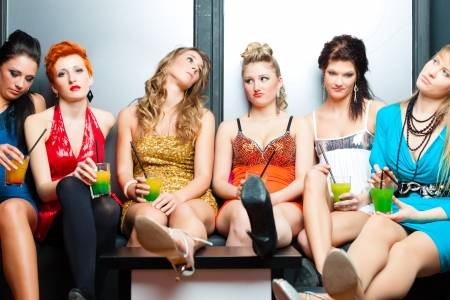 boring: Women or models in club or disco drinking cocktails having no fun as the party is boring Stock Photo