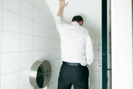 pis: El hombre orinando en el baño Foto de archivo