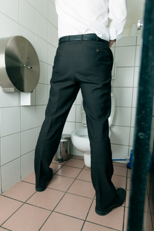 pee: El hombre orinando en el ba�o Foto de archivo