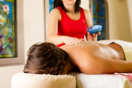 Man receiving a massage in wellness spa by a masseuse photo