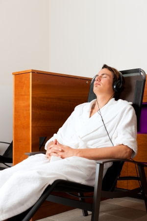 Young man relaxing in spa hearing music with headset in quiet room Stock Photo - 17424869