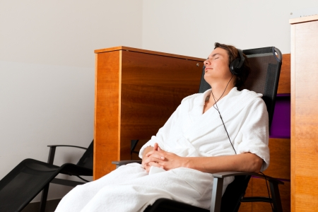 Young man relaxing in spa hearing music with headset in quiet room Stock Photo - 17424843