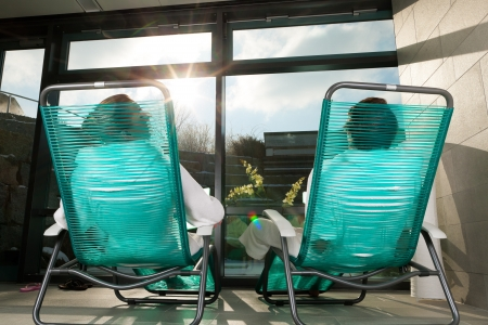 liege: Young couple relaxing in wellness spa on liege, they enjoy the sun Stock Photo