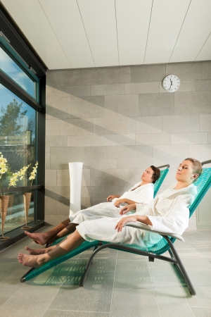 Young couple relaxing in wellness spa on liege, they enjoy the sun photo